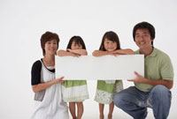 白いボードをもつ4人の家族