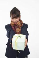 プレゼントを差し出すマフラーをした女子学生 22321025867| 写真素材・ストックフォト・画像・イラスト素材|アマナイメージズ