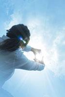 太陽に手をかざす日本人女性