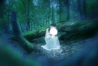 森の中で光るボールを持つ女性
