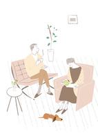 リビングのソファで犬と一緒に読書する高齢女性と男性