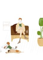 リビングのソファで犬と一緒に読書する父と子