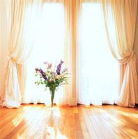 白いカーテンの窓と紫の花
