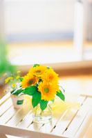 窓際のテーブルに置いた花瓶に入ったひまわり