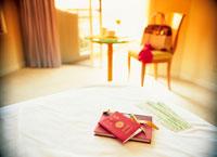 ベッドに置かれたパスポートとチケットと時計