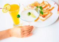 カクテルグラスを持つ手と皿の上の軽食