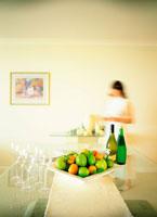 女性とフルーツとグラスとボトル