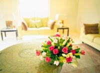 ガラステーブルの上の花とソファ