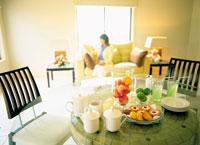 テーブルに用意されたお茶とお菓子とソファに座る女性