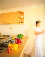 カウンターキッチン上の野菜と女性
