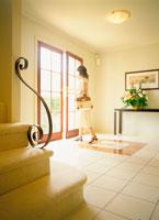 バッグを持ってドアを開ける女性と階段