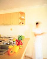 カウンターキッチンに置かれた野菜と女性