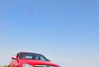 青空と飛行機と女性の乗った赤い車