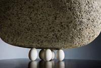 大きな石を支えている5つの卵