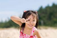 海で遊ぶピースサインの少女