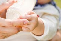 哺乳瓶を持つ赤ちゃんの手