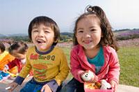 お花畑でお弁当を食べる子供達