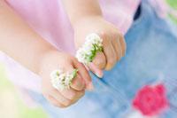 シロツメクサの指輪を付けた女の子の手