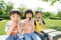 公園でおにぎりを食べる女の子と男の子3人