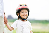 父親と手をつなぐ自転車用ヘルメットをかぶった男の子