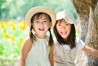 木のそばの笑顔の2人の女の子