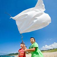 砂浜で白旗を持つ女の子と男の子