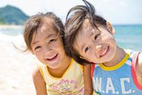 砂浜で微笑む男の子と女の子