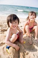 砂浜で遊ぶ水着姿の男の子と女の子