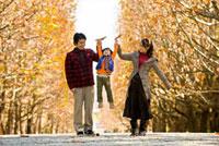 紅葉の並木道で手をつなぐ家族
