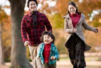 秋の公園で走る家族