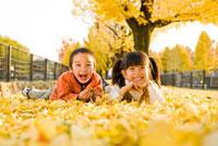 落ち葉に寝転ぶ男の子と女の子 22536003185| 写真素材・ストックフォト・画像・イラスト素材|アマナイメージズ