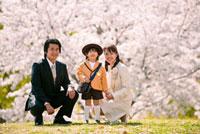 桜の前に立つ入園の男の子と家族