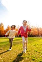 紅葉の公園で走る子供