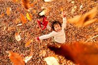 落ち葉を投げて遊ぶ子供