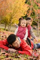 秋の公園で子どもと遊ぶ父親