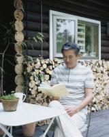 デッキで読書するシニア男性