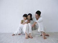 床でくつろぐ家族3人 22600002691| 写真素材・ストックフォト・画像・イラスト素材|アマナイメージズ