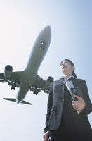 飛行機を背にしたビジネスウーマン