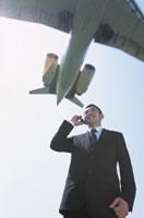 飛行機を背にしたビジネスマン