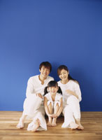 床でくつろぐ家族3人