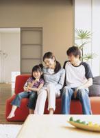 ソファでくつろぐ家族3人