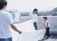 屋上で洗濯物を干す家族3人 22600002815| 写真素材・ストックフォト・画像・イラスト素材|アマナイメージズ