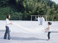 屋上で洗濯物を干す母娘