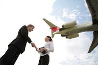 飛行機を背に握手するビジネスマン男女