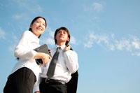 空を見上げるビジネスマン男女