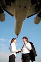 飛行機を背にするビジネスマン男女