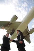飛行機を背に握手する2人のビジネスマン