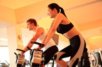 エアロバイクでトレーニングする男女