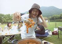 バーベキューで料理を見せる女性