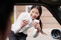 買ったコーヒーを車へ持ちこむ女性